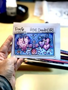 Super Doodle Girl drawing of hearts colored with pink, purple, and blue.